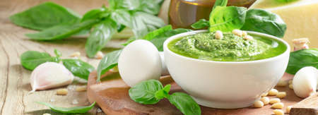 Italian Pesto sauce with green basil, garlic, parmesan cheese, cedar nuts and olive oil, in mortar with pestle, selective focus