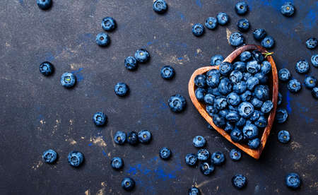 Fresh blueberries in a wooden bowl in the shape of a heart on a dark background, top view