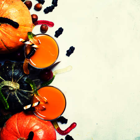 Halloween background with pumpkin juice, disgusting worms and black sweets, top view Stok Fotoğraf