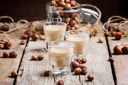 Creamy liqueur with hazelnuts, vintage wooden background, selective focus