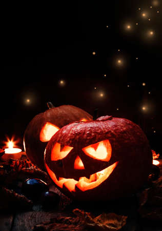 Two Halloween pumpkin Jack-o-Lantern on dark wooden background with fallen leaves and flames, selective focus Imagens