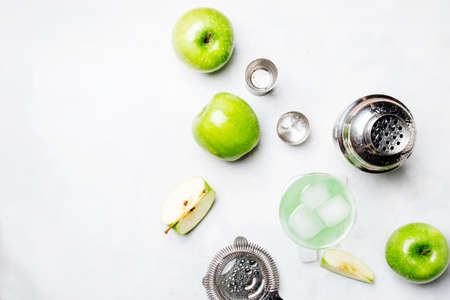 Alcoholic cocktail with green apple and dry vermouth, syrup, lemon juice and ice cubes. Bar tools, gray stone background, top view