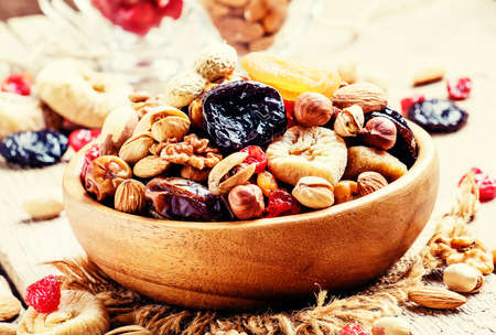 Healthy food: nuts and dried fruit, vintage wooden background, selective focus
