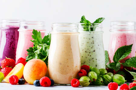 Healthy and useful colorful berry cokctalis, smoothies and milkshakes with yogurt, fresh fruit and berries on gray table, selective focus