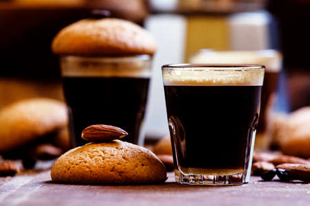 Espresso coffee, amaretti biscuits with almonds, neapolitan coffee maker, vintage wooden background, selective focus