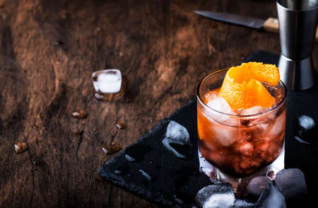 Red cocktail with dry vermouth, bitter, soda, orange zest and ice, wooden bar counter background, bar tools, selective focus