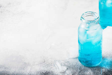 Sport and fitness drink concept, cold isotonic blue water in bottles, gray table background, selective focus
