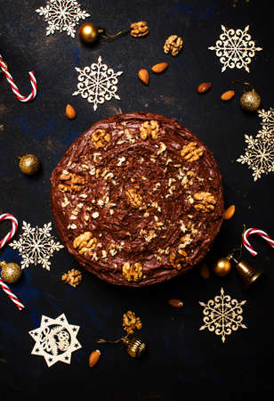 Christmas chocolate cake with nuts, dark background with decoration, top view