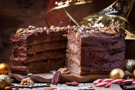 Sliced New Year chocolate cake with walnuts, Christmas dinner, top view 스톡 콘텐츠