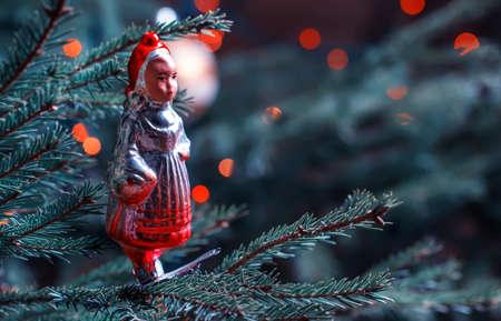 Vintage Christmas toy on the Christmas fir tree, toned image, selective focus