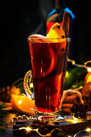 Christmas mulled red wine with spices and fruits in tall glass on wooden rustic table. Traditional Christmas hot drink in festive table setting