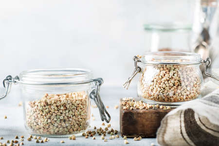 Green buckwheat in glass jar, healthy vegetarian food or raw foods concept, gray kitchen table background, selective focus