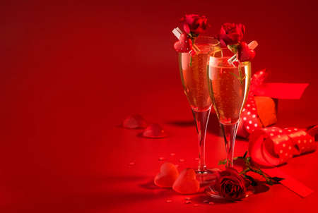 Valentines day red background with champagne glasses, hearts and scarlet roses, copy space