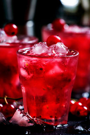 Rosso berry crash, alcoholic cocktail with red currant, vermouth and ice, black background, selective focus