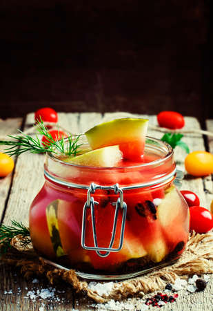 Marinated or pickled watermelon in a glass jar, vintage wooden background, selective focus