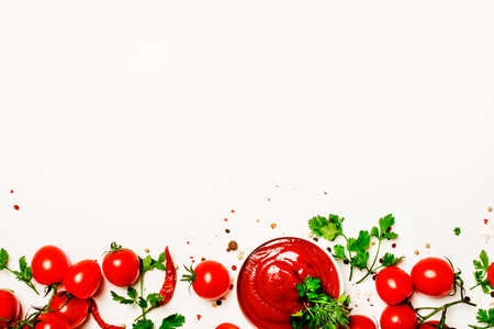 Spicy tomato ketchup sauce with herbs, chili and cherry tomatoes in bowl on white food background, top view