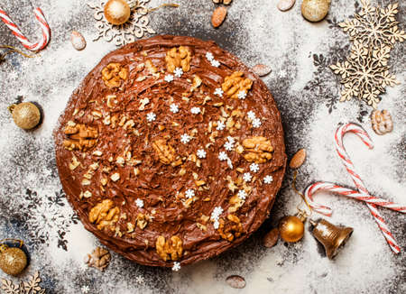 Christmas chocolate cake with nuts, white snow background with new yaers decoration, top view