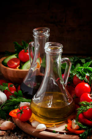 Fresh olive oil in glass carafe with tomatoes, peppers, cucumbers, garlic, herbs and spices on a dark wooden background, selective focus