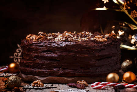 Christmas chocolate cake with nuts, dark background with festive decoration, selective focus