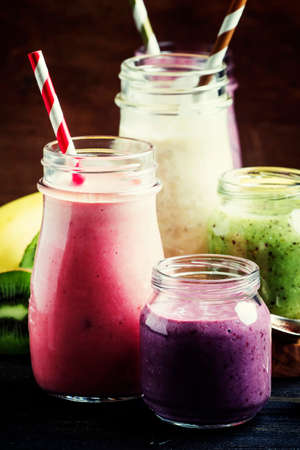 Multicolored milkshakes and berry smoothies, vintage wood background, selective focus