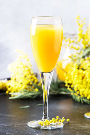 Festive alcohol cocktail mimosa with orange juice and cold dry champagne or sparkling wine in glasses, gray bar counter background with flowers, place for text, selective focus Archivio Fotografico