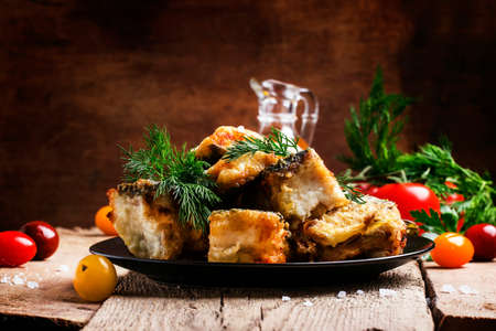 Fried fish, pieces of mullet with dill on a plate. Vintage wooden background, selective focus