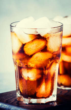 Alcoholic cocktail of rum-cola with ice, gray background, selective focus
