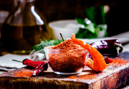 Ground dried red cayenne pepper, rustic style, selective focus on the contents of the bowl