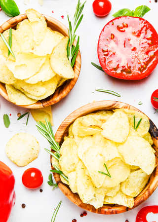 Unhealthy food background, potato chips with salt, tomatoes, chili and bell pepper, spices and green basil, top view Reklamní fotografie
