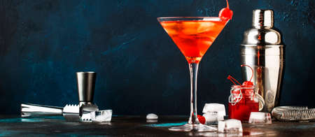 Classic alcoholic cocktail Manhattan with american bourbon, red vermouth, bitter, ice and cocktail cherry in martini glass, night blue brown background, bar tools, copy space, selective focus