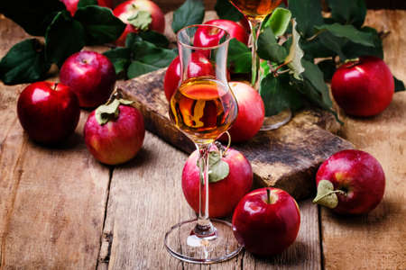 French apple strong alcoholic drink, still life in rustic style, vintage wooden background, selective focus