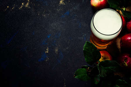 Apple cider in a large beer glass, black background, top view