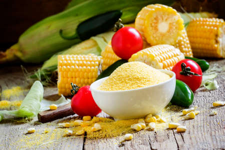 Corn grits, fresh vegetables. Wooden background, rustic style. Selective focus