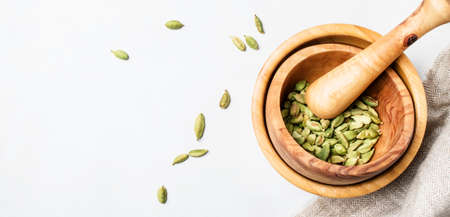 Dried cardamom in wooden bowl with pestle, white background, top view