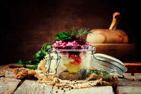 Traditional Russian salad herring under a fur coat, vintage wood background, selective focus