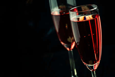 Rose sparkling wine in glasses and white chocolate, dark background, selective focus