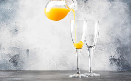 Bartender preparing alcohol cocktail mimosa with orange juice and cold dry champagne or sparkling wine in glasses, gray bar counter background copy space, selective focus