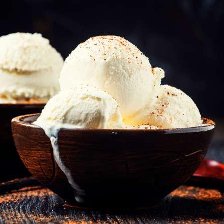 Vanilla ice cream balls, brown bowls, dark background, selective focus