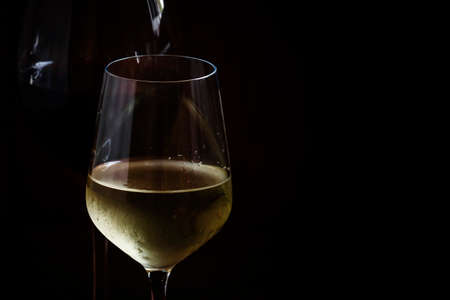 Red and white wine in glasses, dark background, low key, selective focus