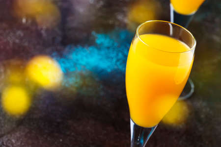 Mimosa alcohol cocktail with orange juice and dry champagne or sparkling wine in glasses, blue background, copy space