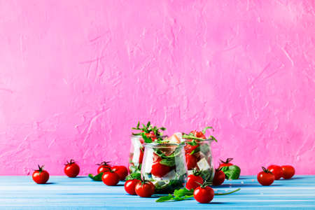 Salad with arugula, cheese, cherry tomatoes and prosciutto in glass jars, pink blue background, selective focus