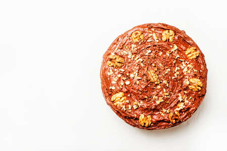 Homemade chocolate cake with nuts, white background, top view