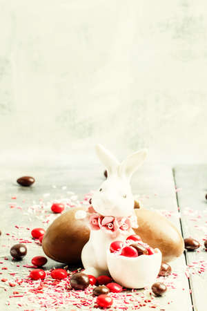 Porcelain Easter bunny with brown and red chocolate eggs and colorful sugar, gray background, selective focus Imagens