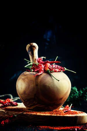 Dry red chili pepper in a mortar and pestle, dark background, selective focus