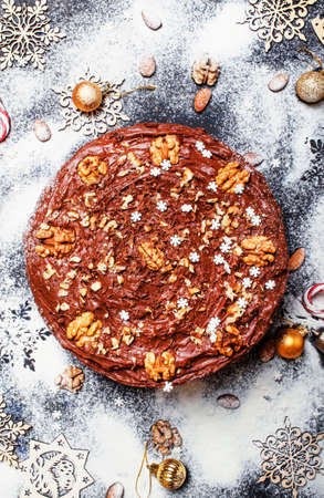 New Year chocolate cake with walnuts, white snow background with christmas decoration, top view