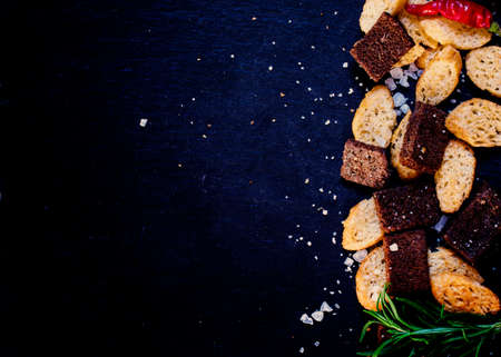 Unhealthy food concept, spicy salted crackers, dark background top view Reklamní fotografie