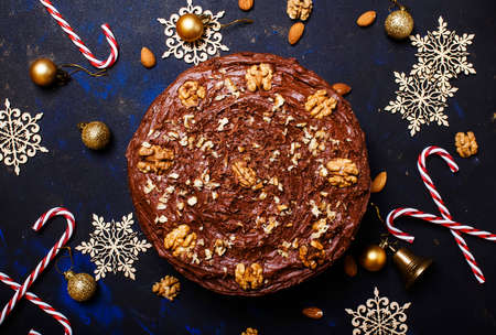 New Year chocolate cake with walnuts, dark background with christmas decoration, top view 스톡 콘텐츠