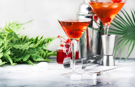 Classic alcoholic cocktail Manhattan with bourbon, red vemuth, bitter, ice and cocktail cherry in glass, gray bar counter background, place for text, selective focus Stock Photo