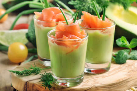 Appetizer with salted salmon and avocado cream with green onion, selective focus