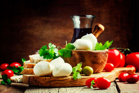 Mozzarella cheese, bread, olives and tomatoes, snack plate. Vintage wooden background, selective focus Stockfoto